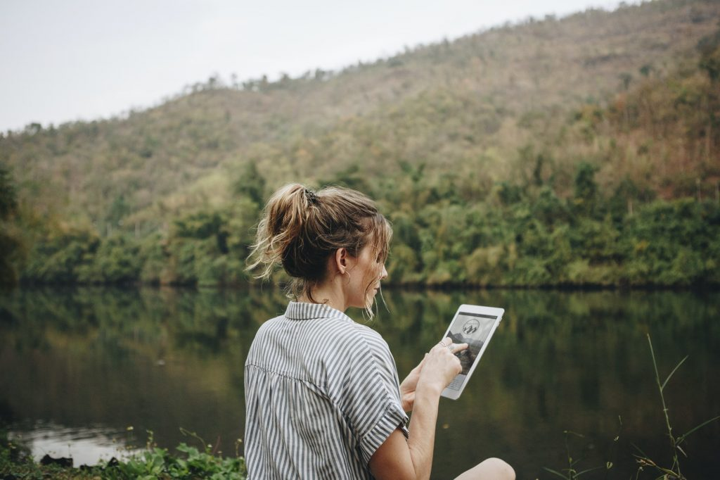 Woman alone in nature using a digital tablet internet connection and travel concept